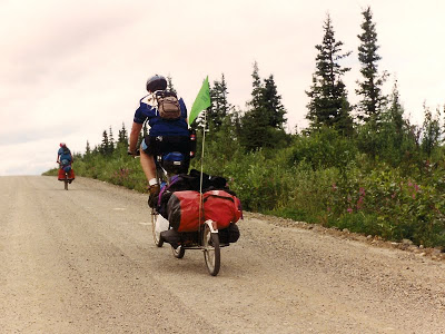 Rear view of two cyclists pedaling away.