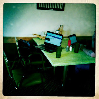 A small working area with laptop on a desk and chairs.