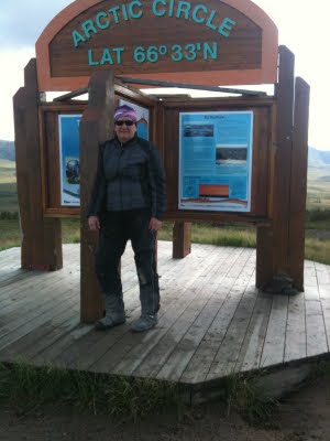 """Judy standing in front of a sign reading, """"Arctic Circle Lat 66 degrees 33'N"""""""