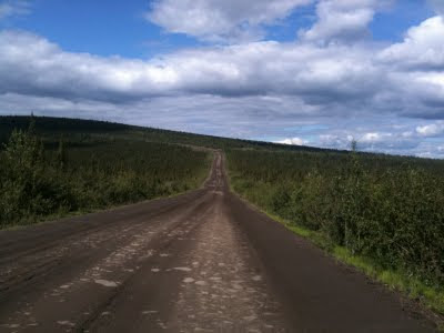 A long dirt road travelling away into the distance