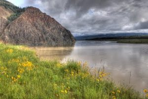 The Yukon River in the summer with a cloudy sky.