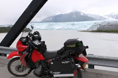 Motorcycle leaning against the side of the road with a glacier in the background.