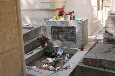 Jim Morrison's grave with lots of flowers and memorabilia