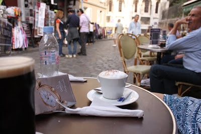 A cappuccino with lots of foam on a table outside in France.