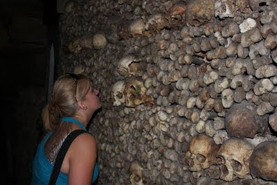 Nikole closely looking at skulls embedded in the wall