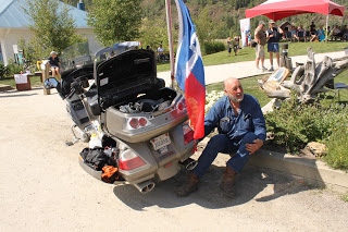 A man sitting next to his large motorcycle with a massive Texas flag protruding from the back