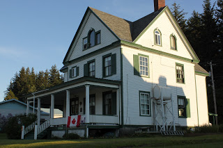 A large white building with green trim and a Canada flag draped over the front entrance way