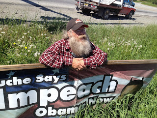 A man with a long white beard leaning against a sign to impeach Obama