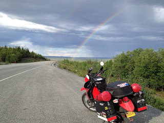 Judy's motorcycle parked on the side of the road with a beautiful rainbow in the sky above.