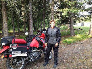 Judy in all of her riding gear and standing in front of her motorcycle