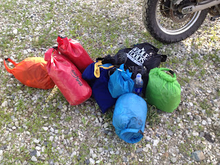 Several small colorful sacks on the ground next to the tire of a motorcycle