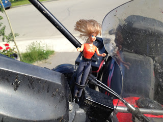 Barbie secured to the front of the motorcycle with her hair very wind blown