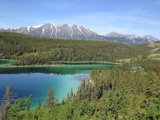 Gorgeous teal colored lake surrounded by greenery and snow-capped mountains