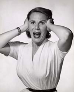 A black and white photo of a woman grasping her head with both hands and screaming