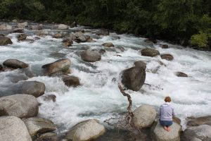 Kim sitting barefoot on a large rock while the Little Susitna River rages past