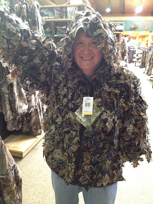 Judy standing in a store while covered in camo attire