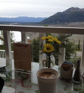 A table with a mug of coffee, fresh flowers, and a menu, outside on a deck with mountains in the background