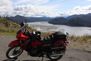 Judy's motorcycle parked with the Copper River in the background surrounded by mountains and a cloudy sky