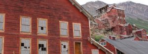 Image of the red buildings of Kennecott, with the collapsing mine in the background