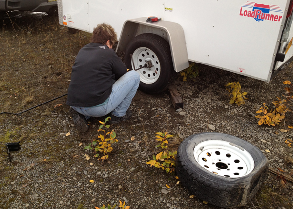 Image of Judy changing a flat tire on trailer
