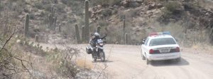 Image of Judy on her motorcycle waving at the passing cop car