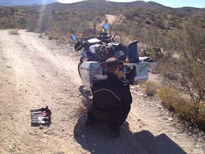 Image of Michael kneeling behind his motorcycle repairing the license plate