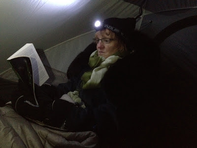 Image of Kim reading by headlamp in a tent