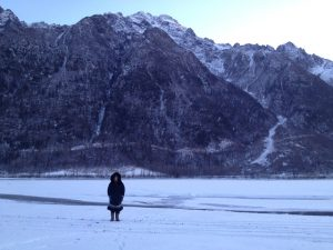 Image of Kim standing in her parka with massive mountains in the background