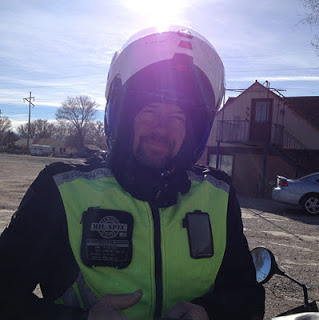 Image of Michael in motorcycling attire with a lifted helmet and smiling
