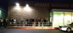 Image of a long line outside of the entrance to the liquor store