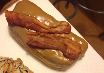 Image of a maple doughnut with two slices of bacon atop