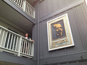 Image of Jaz standing on a balcony with a portrait of Steinbeck