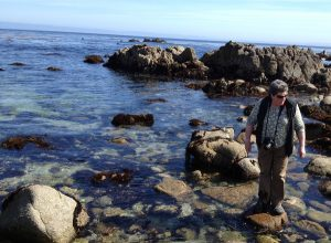 Image of Jaz walking across the rocks in the water while wearing pants