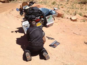 Image of Michael repairing the broken chain guard on motorcycle