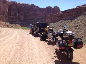 Image of two motorcycles parked on the side of a dirt road with the camera crew's Jeep in front.