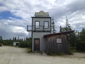 "Image of a very small building with a sign atop reading, ""Welcome to Dawson City"""