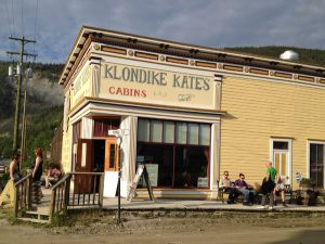 "Image of a yellow building with a sign reading, ""Klondike Kate's Cabins"""