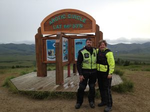 "Image of Michael and Judy, in full motorcycle attire, standing in front of a sign reading, ""Arctic Circle 66°33′N"""