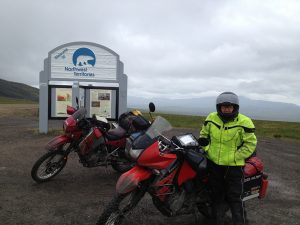 "Image of Judy in full motorcycle attire, looking cold, standing in front of a sign reading, ""Welcome to Northwest Territories"""