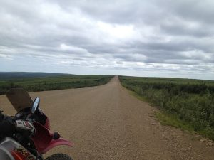 Image of a photo, taken from atop a motorcycle, of long dirt road