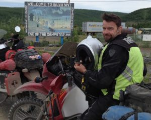 "Image of Michael sitting atop his motorcycle in front of a sign reading, ""Welcome to Inuvik End of the Dempster"""