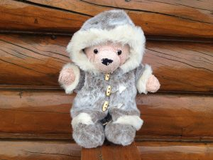 Image of a little orange teddy bear (Poopy) wearing a fur parka