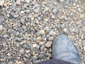 Image of a motorcycle boot atop gravel