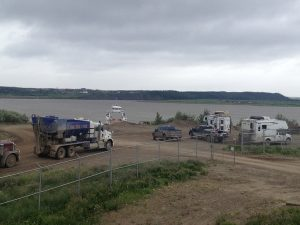 Image of several trucks and cars stopped at the end of a dirt road with the water in the background