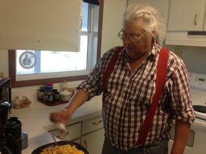 Image of a white-haired man cooking Mac and Cheese on a stove