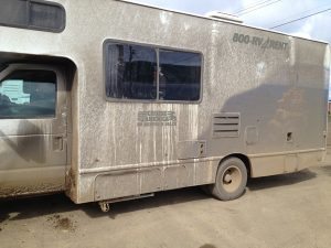 Image of the side of a large motorhome covered in dirt