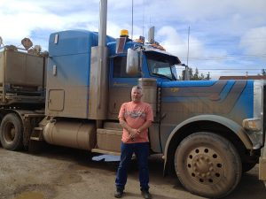 Image of a trucker (Dave) standing outside of his large mud covered truck