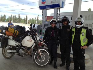 Image of Sigrid, Bjoern, and Michael at a gas station standing in front of two motorcycles