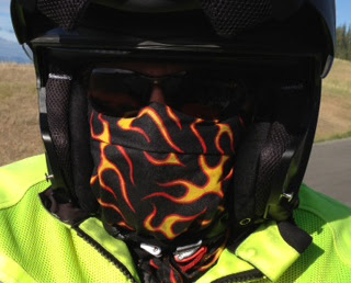 Image of Judy wearing motorcycle helmet and a scarf with flames print around her face with sunglasses; her face is completely covered.