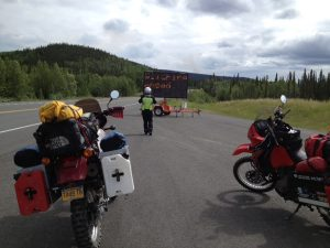 Image of two motorcycles stopped on the road in front of a road sign warning of wildfires